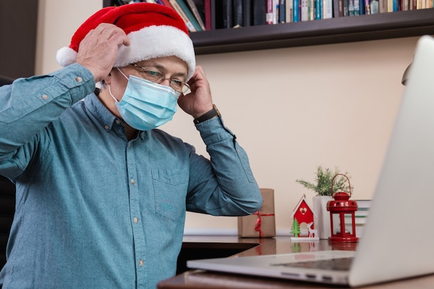 Senior man in santa claus hat put on face mask and talks using laptop device. the room is festively decorated. christmas during coronavirus.