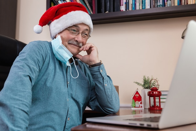 Senior man in santa claus hat talks using laptop for video call friends and childrens. the room is festively decorated. christmas during coronavirus.