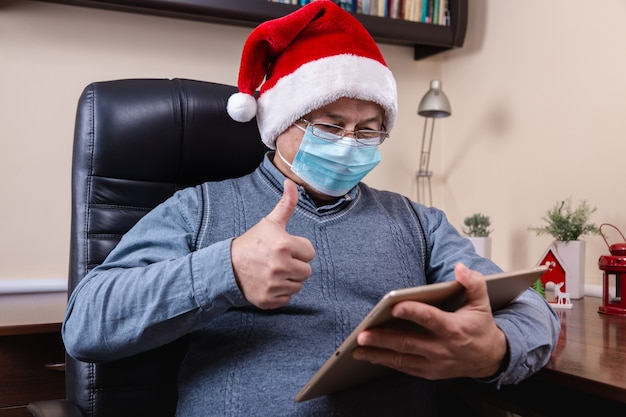 Senior man in santa claus hat talks using tablet device for video call friends and childrens. the room is festively decorated. christmas during coronavirus.