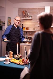 美味しさとワインとの関係を祝いながら妻に仕える年配の男性。老夫婦が話し、台所のテーブルに座って、食事を楽しんで、結婚記念日を祝います。