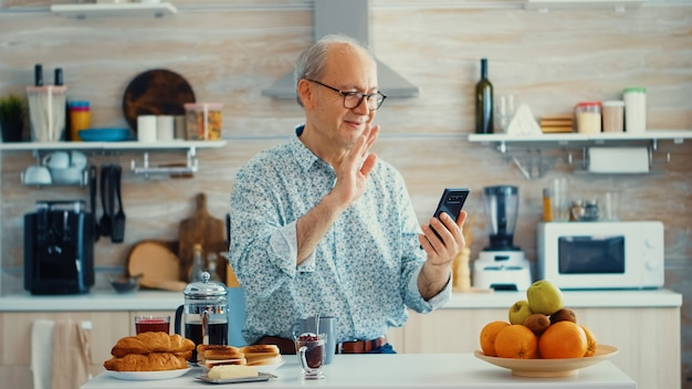 Senior man shacking hand during a video call in kitchen using smartphone. elderly person using internet online chat technology video webcam making a video call connection camera communication conferen
