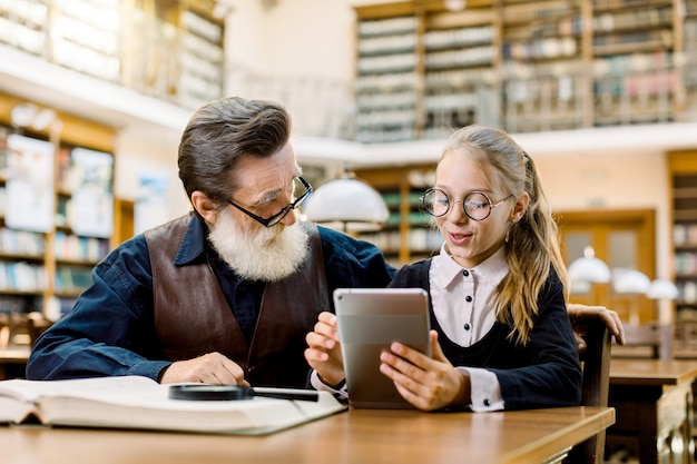 Senior man in shirt and leather vest and little pretty girl granddaughter looking at a tablet, while sitting and studying together in library. old book shelves on the background