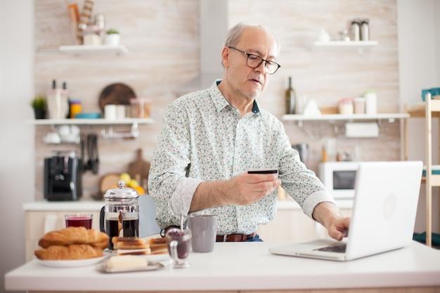 彼の家の快適さからオンラインで買い物をしている年配の男性。年金受給者は、キッチンでの朝食時にクレジットカードとラップトップからのアプリケーションを使用してオンラインで支払います。インターネットpaymeを使用して退職した高齢者