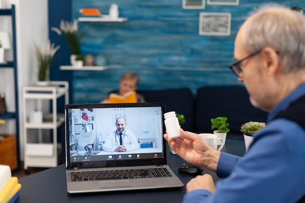 Старший мужчина показывает бутылку с таблетками доктора на веб-камеру во время видеозвонка. пожилой мужчина обсуждает со здоровьем ...