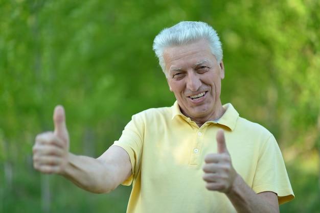 여름 n 배경에 서 있는 엄지손가락을 보여주는 수석 남자