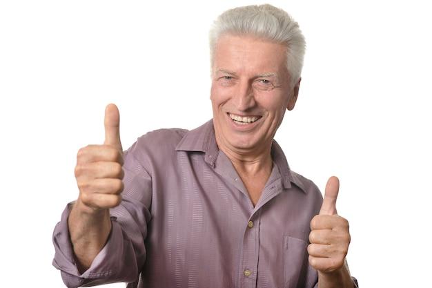 흰색 배경에 서 있는 엄지손가락을 보여주는 수석 남자