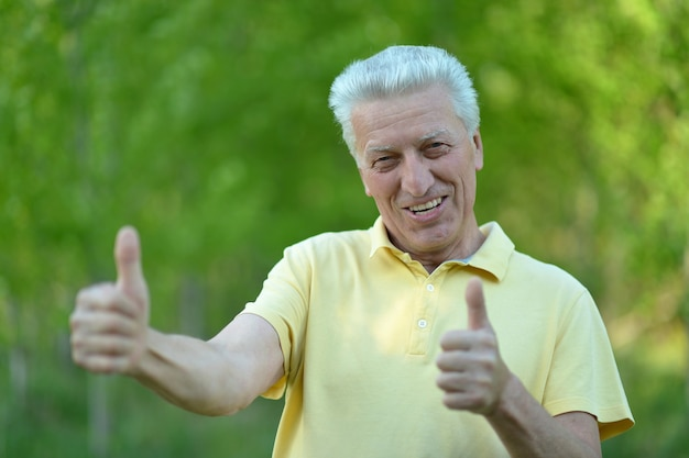 Senior man showing thumbs up standing on summer n background