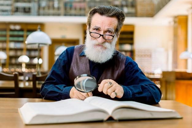 年配の男性はビンテージライブラリに座って、虫眼鏡を保持し、本を読みます。ライブラリで働くヴィンテージのシャツと革のベストのひげを生やした男