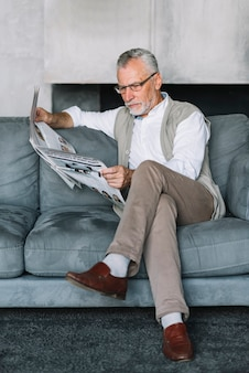 Senior man sitting on cozy sofa with crossed leg reading newspaper