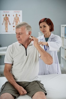 Senior man sitting on examination bed in medical office and complaining about pain in neck and shoulder