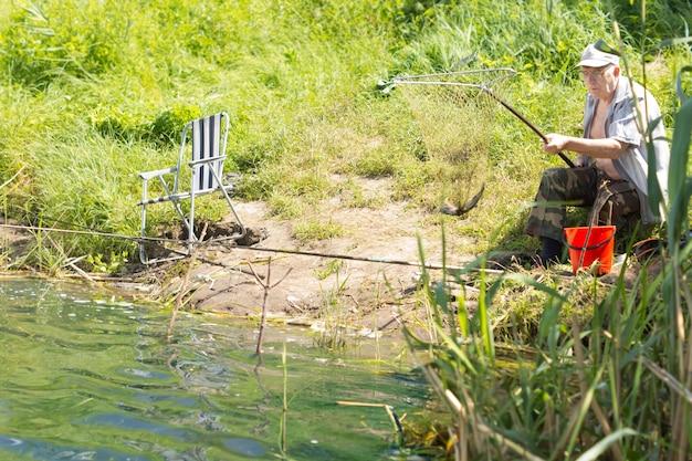 호수 가장자리에 앉아 낚시 수석 남자