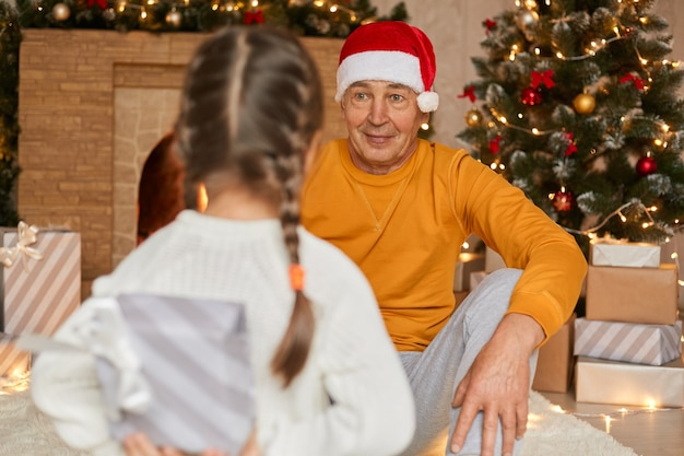Senior man sitting on floor in santa cap and yellow sweater and looking at his granddaughter posing backwards to camera and hiding present box for grandad, child giving christmas gift to grandfather.