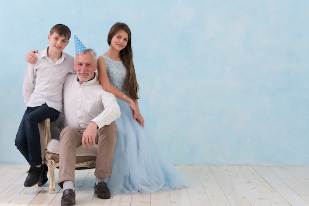 Senior man sitting his grandchildren on arm chair looking at camera