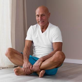 Старший мужчина сидит в позе лотоса йоги