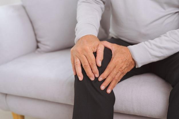 집 거실 소파에 앉아 고통으로 무릎을 만지는 노인