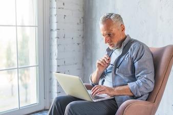 Senior man sitting on armchair using laptop
