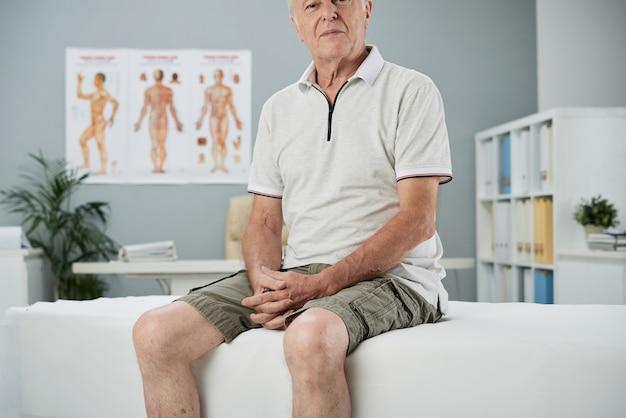 理学療法士を待っている診療所の診察台に座っている年配の男性