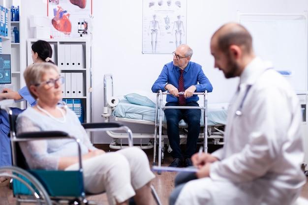 相談のために歩行フレームのwaintingと病院のベッドに座っている年配の男性