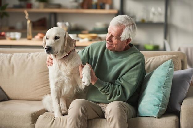Старший мужчина сидит на диване вместе со своей собакой в свободное время дома