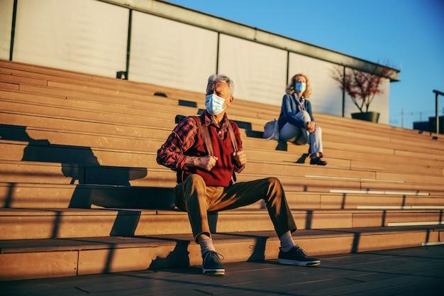 Старший мужчина сидит на лестнице и в защитной хирургической маске.
