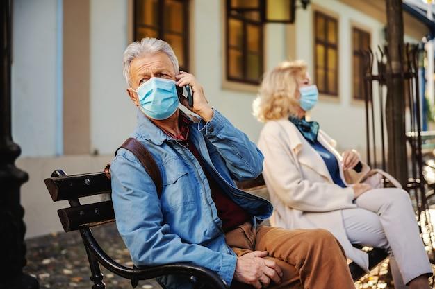 Старший мужчина сидит на скамейке снаружи. на нем защитная маска.