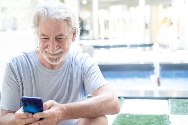 笑顔の携帯電話を使用して屋外に座っている年配の男性