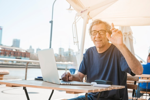 Senior man sitting at a restaurant table with laptop calling the waiter