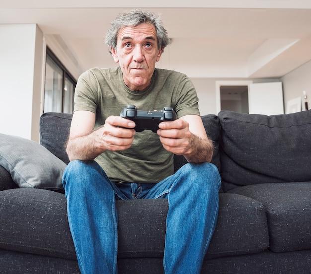 Senior man sitting on sofa playing video game with joystick