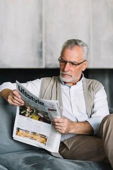 Senior man sitting on sofa reading newspaper
