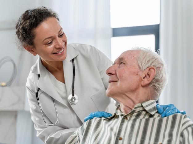 Senior uomo seduto in sedia a rotelle accanto a un medico