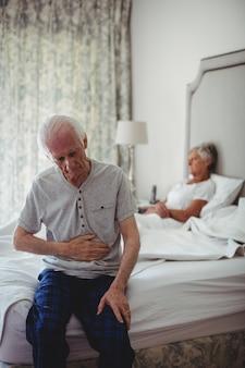 寝室に座って胃に手で座っている年配の男性人