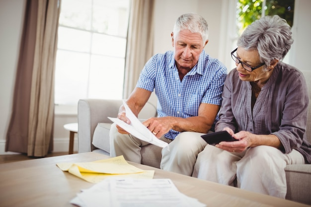 Senior man sitting with woman on sofa and showing documents in living room
