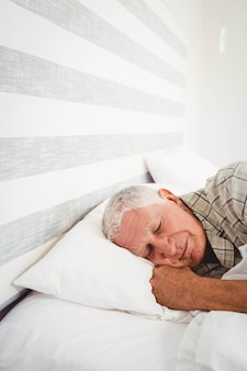 Senior man sleeping on bed in bedroom