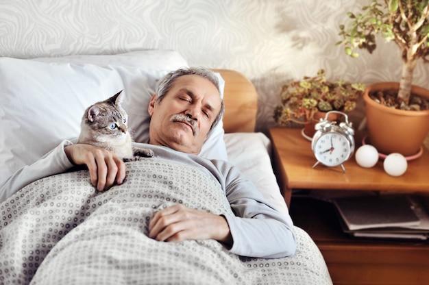 Старший мужчина спит в постели в компании своего кота Premium Фотографии