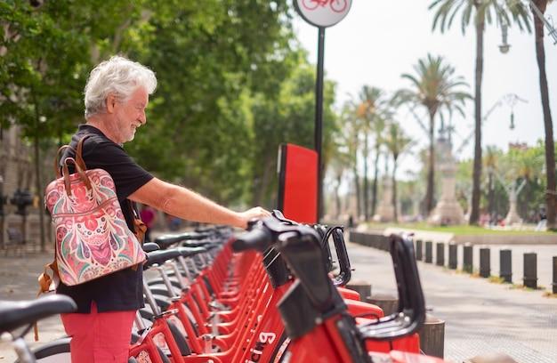 공공 공원에서 전기 자전거를 임대하는 노인 미소. 자유와 건강한 생활 방식을 즐기는 수염 난 백인 사람들
