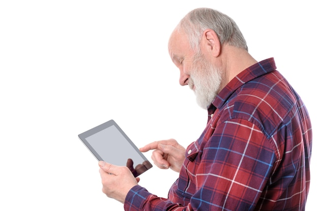 Senior man smiling while doing with something at screen of tablet computer isolated on white