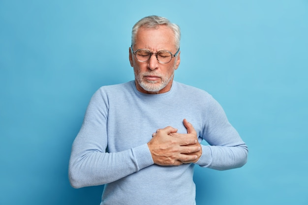 Senior man in spectacles presses hand to chest has heart attack suffers from unbearable pain closes eyes wears optical glasses poses against blue wall