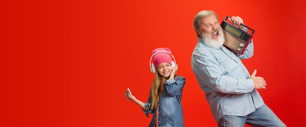 Senior man spending happy time with granddaughter on red