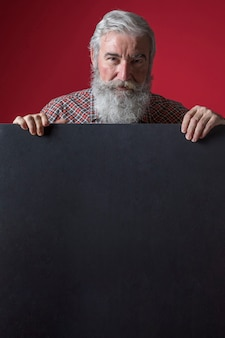Senior man standing behind the black placard against red background