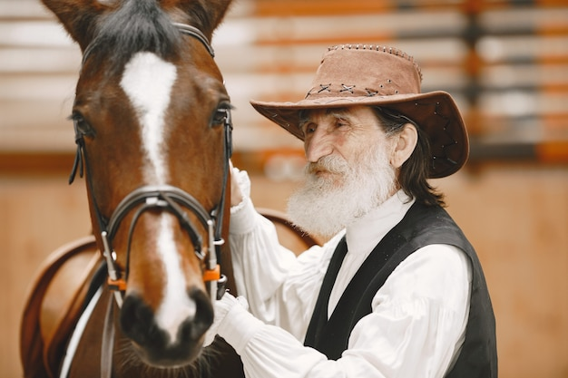 A senior man standing close to a horse outdoors in nature