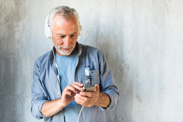 Senior man standing in front of concrete wall listening music on headphone