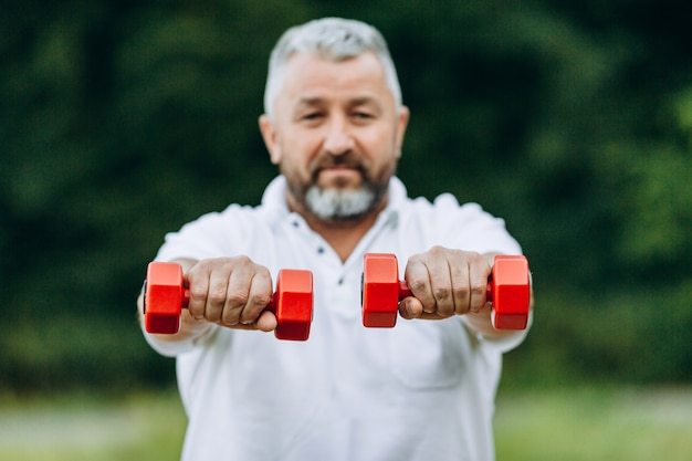 Senior  man standing  holding  a dumbbells in a  straight hands. dumbbells in a focus