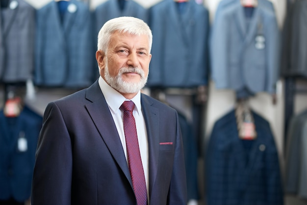 남자를위한 상점 옷에 서있는 수석 남자.