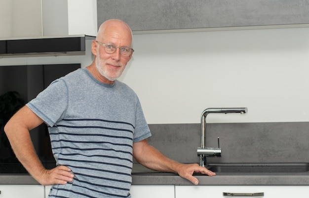 Senior man standing in the kitchen