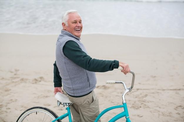 Старший мужчина стоял с велосипедом на пляже