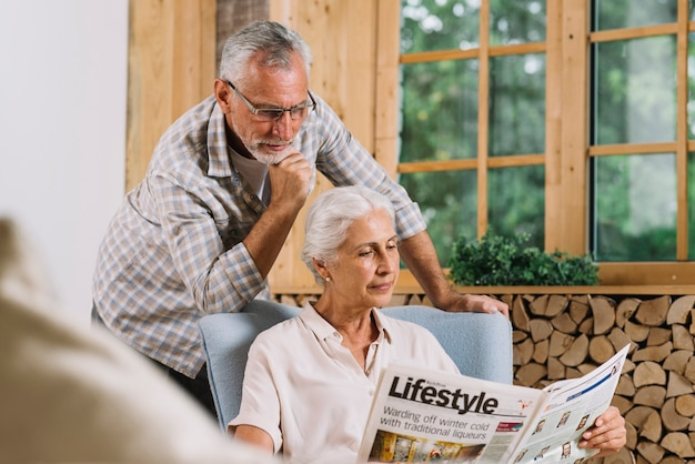 Senior man standing behind the woman sitting on chair reading newspaper