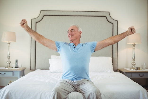 Senior man stretching arms on bed