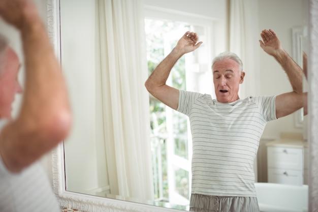 Старший мужчина, растягиваясь перед зеркалом