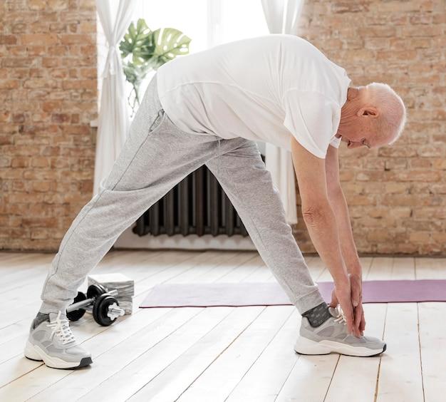 Senior man stretching indoors full shot
