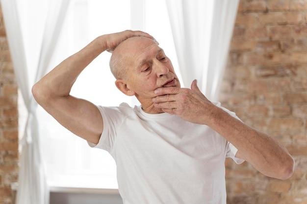 Старший мужчина, растягивая шею
